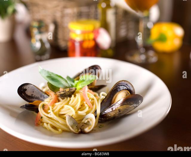 Italienische Spaghetti mit Muscheln und Basilikum auf einem Holztisch Stockbild