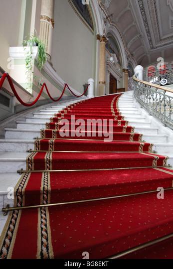 Marmor-einen Schritt, der von einem roten Teppich abgedeckt Stockbild