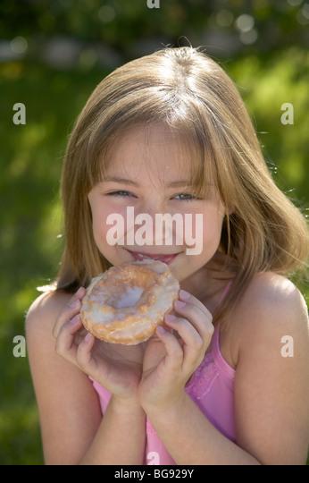 Mädchen halten alte altmodische Donut außerhalb Stockbild