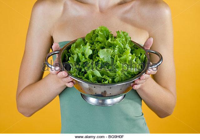Eine junge Frau mit einem Sieb voller Salat Stockbild