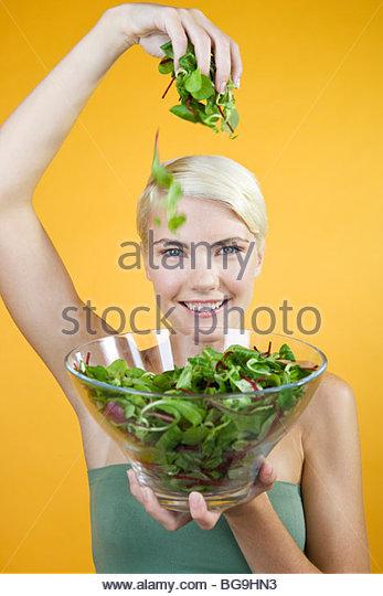 Eine junge Frau hält eine Schüssel mit Salat Stockbild