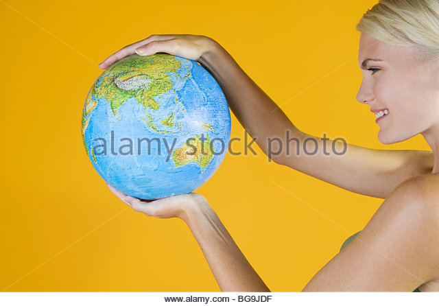 Eine junge Frau hält einen Globus Stockbild