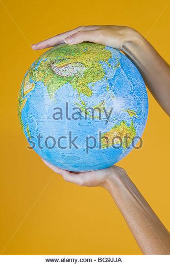 Hände halten einen Globus Stockbild
