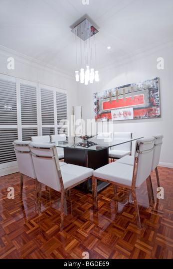 Luxus nach Hause Esszimmer Interieur mit dunklen braunen Holzböden und weißem Leder Essplatz Stockbild