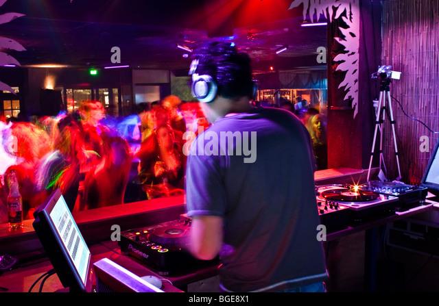 DJ-mixing in einem Nachtclub voller Tänzer Stockbild
