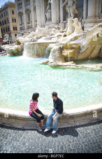 Junges Paar sitzt am Trevi-Brunnen Stockbild
