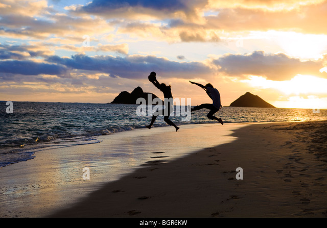 Silhouette der Zwillingsbrüder mit Trommel und Gitarre springen in der Luft bei Sonnenaufgang am Strand von Stockbild