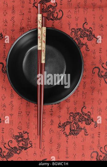 Orientalische Keramikschale und Stäbchen auf traditionellen günstigen Hintergrund. Stockbild