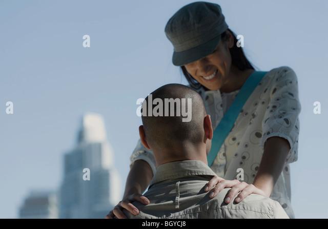 Junges Paar, Mann sitzend, Frau, die vorn mit Händen auf den Schultern des Mannes blickte lächelnd platziert Stockbild