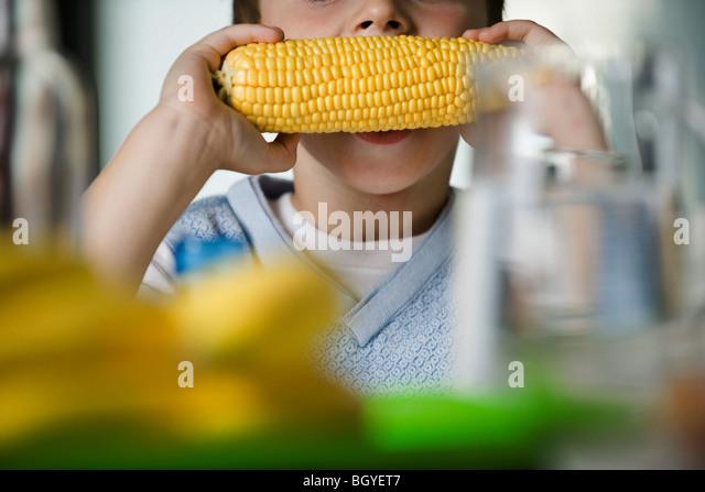 Junge Essen Mais auf Maiskolben, beschnitten Stockbild