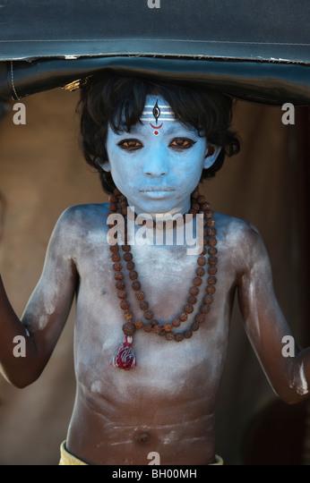 Indischen jungen Gesicht gemalt als die Hindu-Gott Shiva stehen in einer Rikscha Stockbild