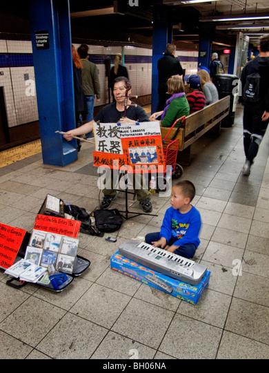 Eine asiatische Musiker wird von seinem kleinen Sohn begleitet, wie sie ein Duett für Spenden an einer u-Bahnstation Stockbild