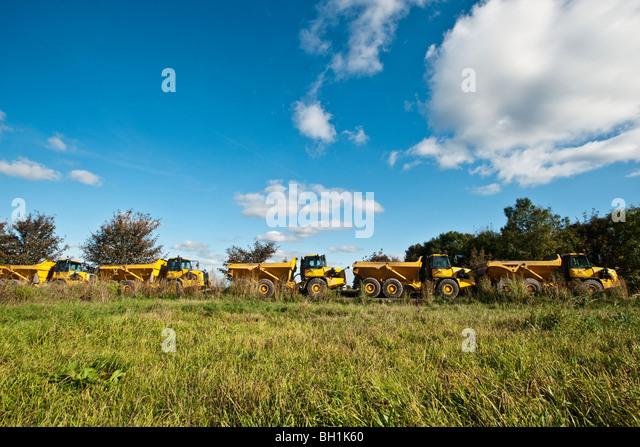 Reihen von Baufahrzeuge im Feld Stockbild