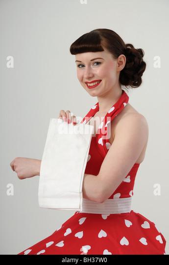Frau im Kleid im Stil der 1950er Jahre hält eine Tischdecke Stockbild