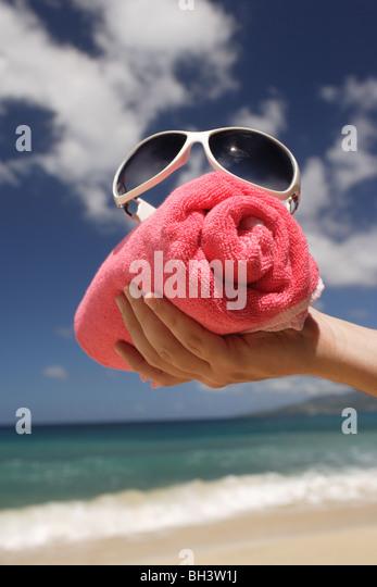 Die Hand eines Mannes hält eine gerollte rote Badetuch und eine weiße Sonnenbrille an einem tropischen Stockbild