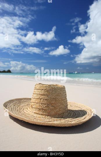 Einen Strohhut auf dem Sand auf einem einsamen tropischen Strand liegen Stockbild