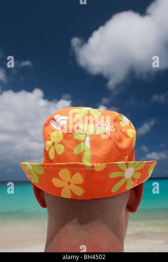 Nahaufnahme eines Mannes mit einem bunten Sonnenhut mit Blick auf den Horizont an einem tropischen Strand Stockbild