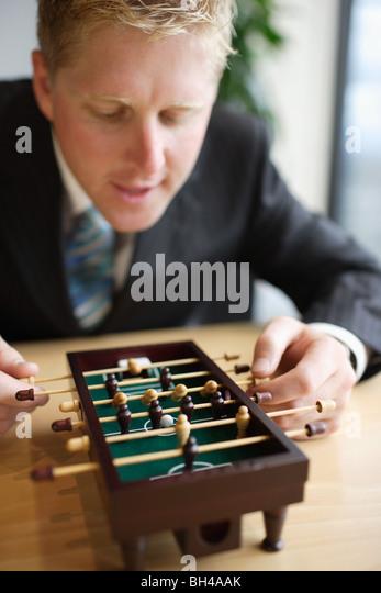 Ein Geschäftsmann Miniatur Tischfußball zu spielen, am Schreibtisch, Lächeln Stockbild