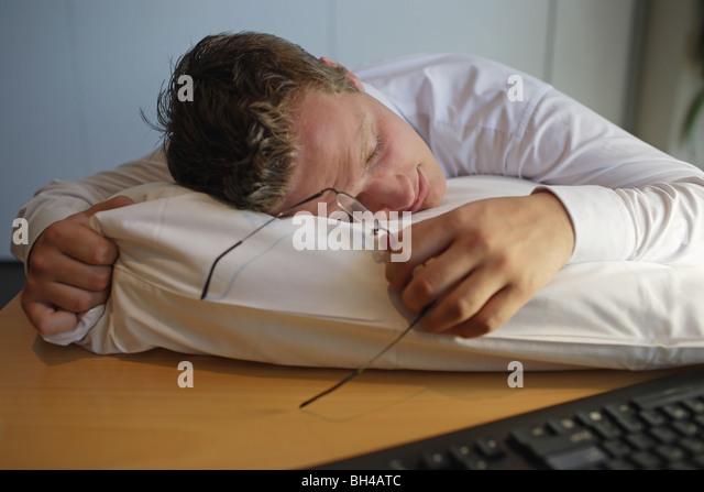 Junger Geschäftsmann schlief auf einem Kissen auf Schreibtisch Stockbild