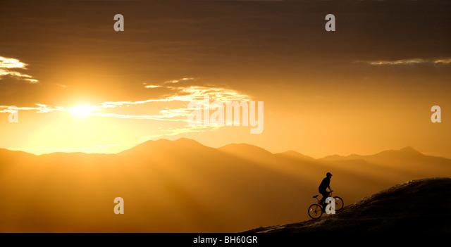 Mountainbiker reitet auf einem Hügel bei Sonnenuntergang. Dieser ist in Arizona, westlich von Tucson. Stockbild