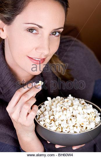 Eine Mitte Frau Essen popcorn Stockbild