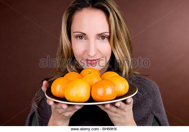 Eine Mitte Frau Halteplatte Clementinen Stockbild