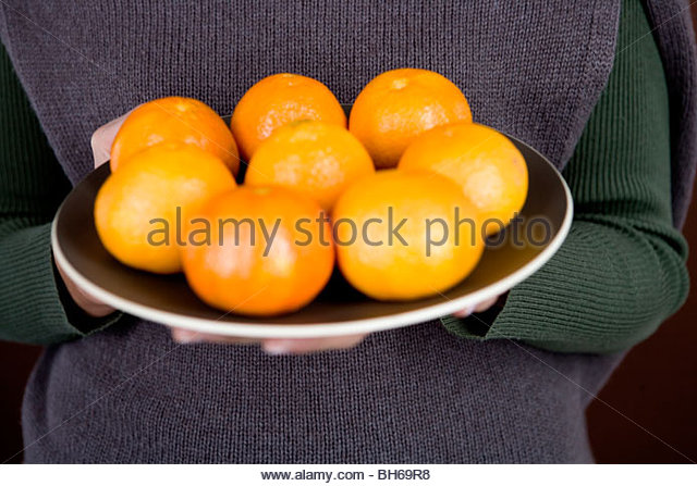 Eine Frau hält einen Teller mit Clementinen Stockbild