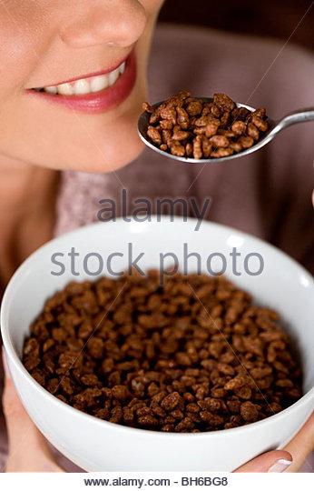 Eine Mitte Frau essen eine Schale mit Schokolade beschichtete Getreide Stockbild