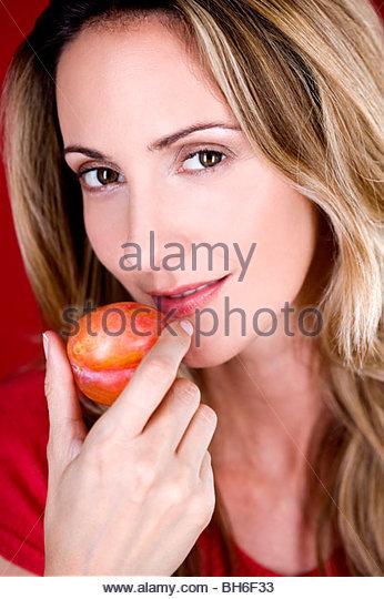 Eine Mitte Frau essen eine Pflaume Stockbild