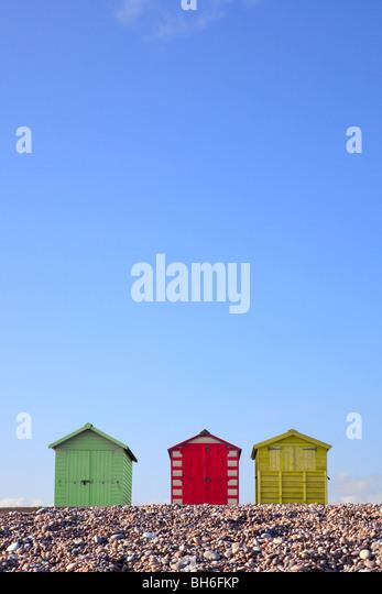 Drei bunte Strandhütten gegen ein strahlend blauer Himmel, gerahmt um textfreiraum im oberen Teil des Bildes Stockbild