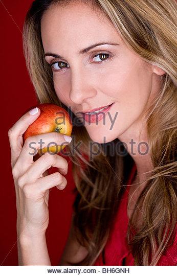 Eine Mitte Frau einen Apfel essen Stockbild