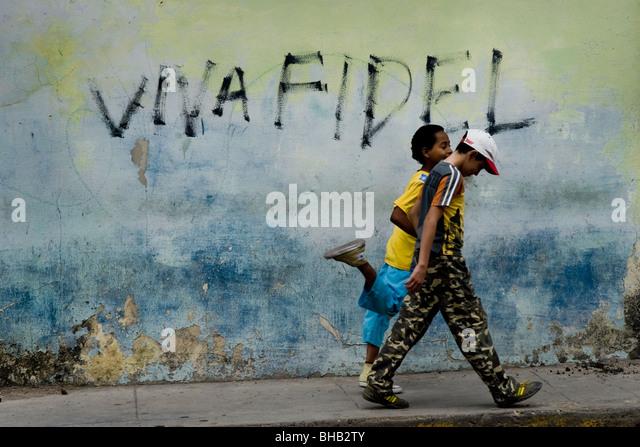 Kubanischen Jungen zu Fuß vor einer Propaganda schreiben, feiert Staatschef Fidel Castro, gemalt an der Wand Stockbild