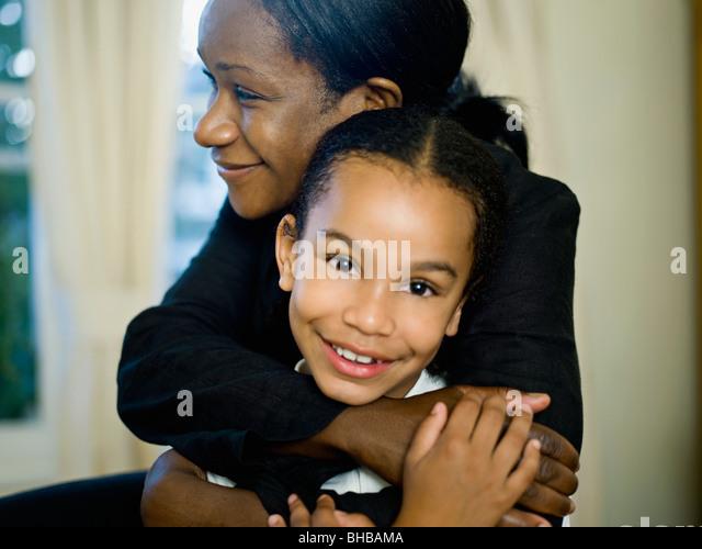 Eine Mutter ihre kleine Tochter umarmt Stockbild