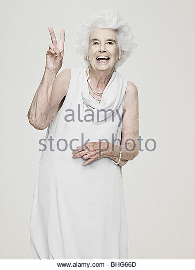 Ältere Frau macht ein Friedenszeichen Stockbild