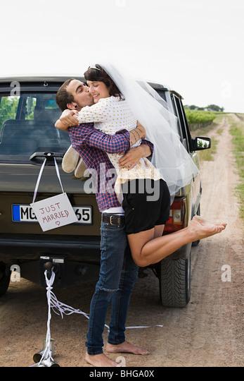 Brautpaar mit einem Fahrzeug Stockbild