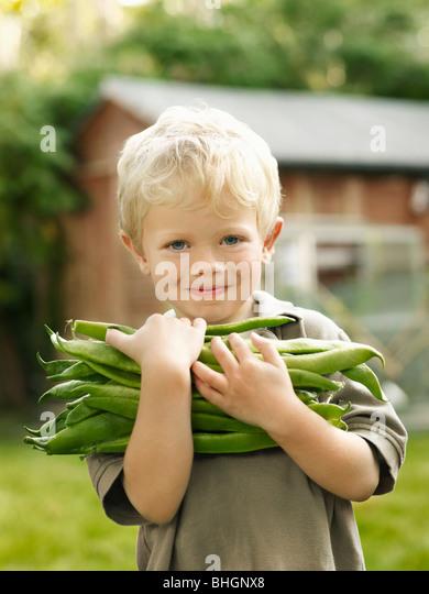 kleiner Junge hält Garten produzieren außerhalb Stockbild