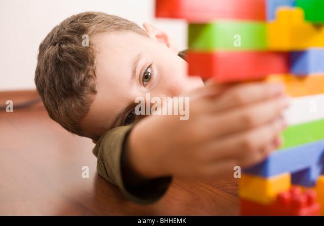 8 Jahre alter Junge mit bunten Würfel auf dem Boden spielen Stockbild