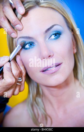 Make-up Artist Lidschatten auftragen, auf eine junge Frau mit offenen Augen Stockbild