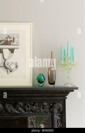 Artwork, Glaswaren und Kandelaber auf geschnitzten Kaminsims Stockbild