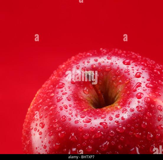 Roter Apfel mit Blatt auf rotem Grund Stockbild