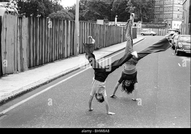 Mädchen im Teenageralter drehen Wagenräder auf der Straße zu spielen. Elefant und Burg Süd-London Stockbild
