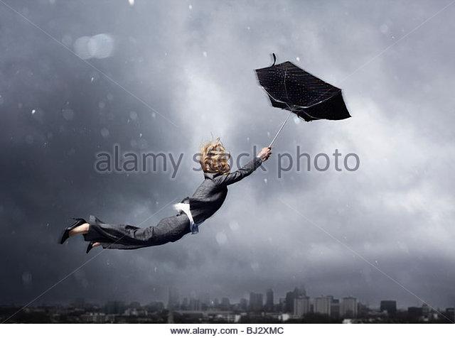 Frau wird von einem Regenschirm geblasen Stockbild
