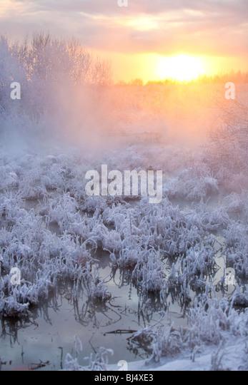 Sonnenuntergang Winterlandschaft. Wasser und gefrorenen Rasen. Stockbild