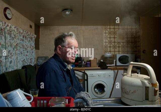 Senior single Mann beobachtet einen Wasserkocher Kochen in seinem Wohnmobil Stockbild