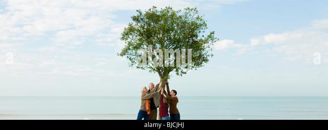 Ökologie-Konzept, Gruppe von Menschen unterstützen Baum zusammen Stockbild