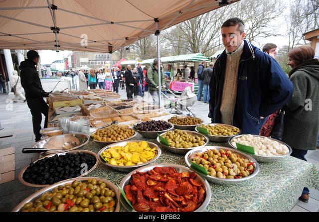 Ein Mann schaut auf einige Oliven auf einem Stall während des Brighton Essen und trinken-Festivals Stockbild