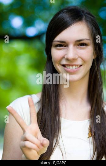 Frau in einem weißen Hemd machen das Friedenszeichen Stockbild