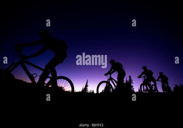 vier Mountainbiker in Folge in der Abenddämmerung Stockbild