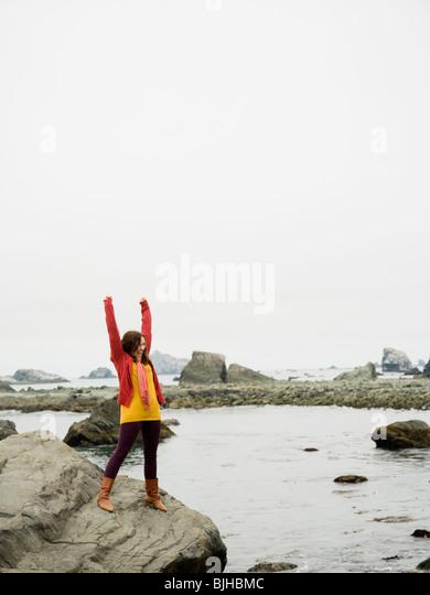 Frau hob die Arme in der Luft auf einem Felsen mit Blick auf eine zerklüftete Küste des Ozeans Stockbild