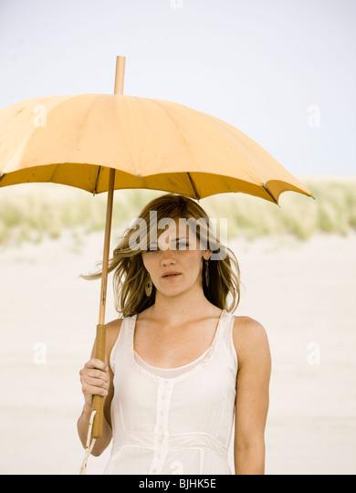 Frau mit Sonnenschirm am Strand Stockbild